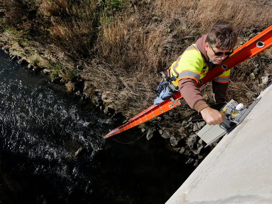 Dan Ceynar, project engineer with the Iowa Flood Center, installs an ultrasonic stream gauge on a bridge east of Pleasant Hill in this Register file photo.