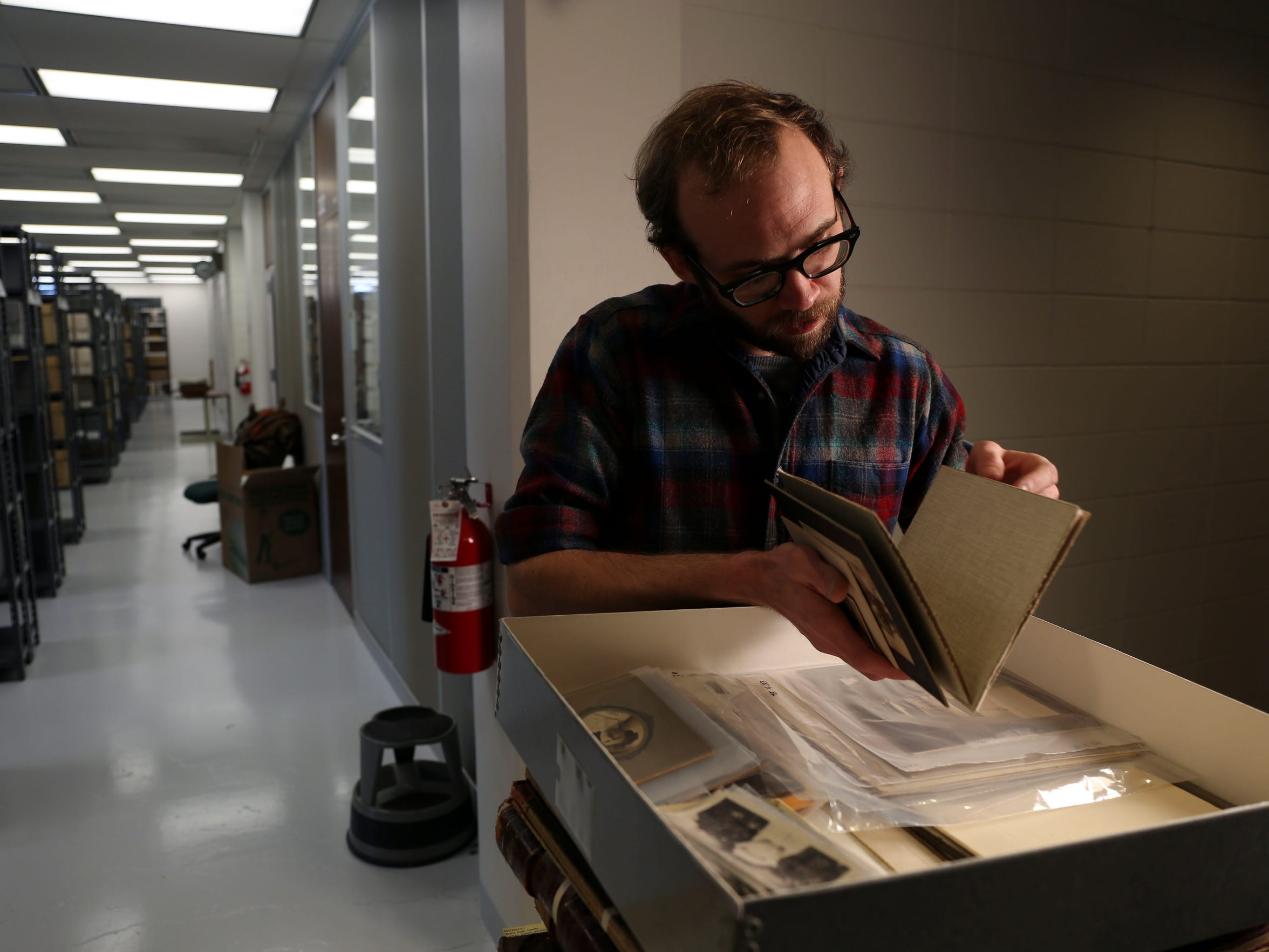 Dustin Wistman, project archivist for the Rural Schools Collection sorts through materials on Tuesday, Jan. 13, 2015, at the Rod Library on the campus of the University of Northern Iowa in Cedar Falls, Iowa.