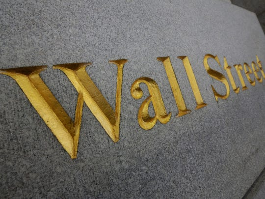 Wall Street is etched in the facade of a building in New York's Financial District. The U.S. stock market is opening sharply lower, Tuesday, Jan. 27, following disappointing corporate earnings and weak economic news. (AP Photo/Richard Drew, File)
