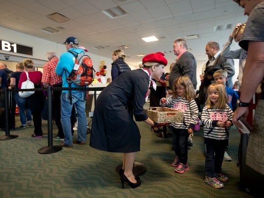 Jennifer Schmidt, an Air Berlin ambassador, offers chocolates to passengers as they board an Air Berlin flight to Dusseldorf on Tuesday.