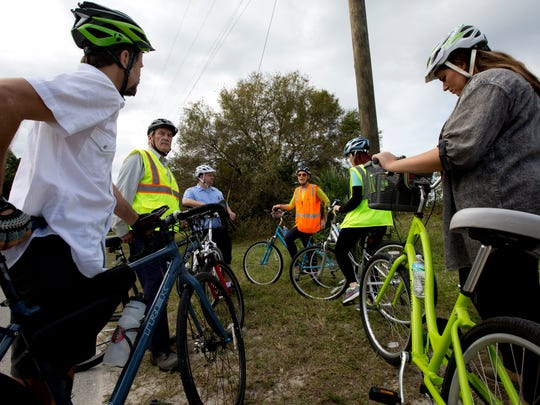 Jenn Hagen, a planner for Bonita Springs, center, speaks during a bike tour of Bonita Springs with Steve Clark from the League of American Cyclists, left, and others on Friday. Clark is visiting Southwest Florida to talk to communities that are interested in apllying to be bike-friendly communities.