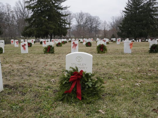 Wreaths adorn the grave marker of veterans Saturday at the Indiana Veterans Home. About 100 people turned out Saturday to participate in the local effort tied to Wreaths Across America. Each year, wreaths are placed at more than 750 national cemeteries and veteran monuments for National Wreaths Across America Day. Locally, 1,800 wreaths were laid at the veterans home.