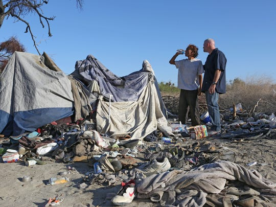 Ernie Vasquez, left, takes a big drink of water with CV Rescue Mission shelter manager Mark McGowan after he and a group from the mission delivered food, water and supplies to homeless near Dillon Rd in Coachella, Wednesday, June 18, 2014.