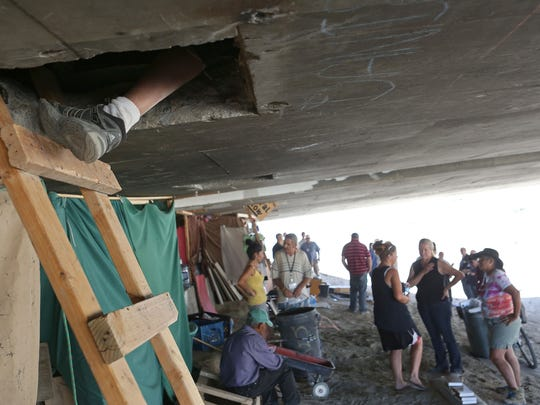 A man rests his foot on a ladder leading up to an area inside of an overpass on Golf Center Dr where he and 15 others live everyday.  The Coachella Valley Rescue Mission had staff helping out the homeless Wednesday distributing food, water and essentials, June 18, 2014.