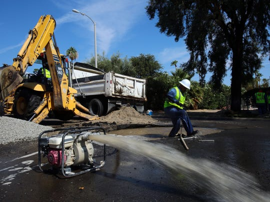 A Coachella Valley Water District crew member emerges from a water-filled hole in the roadway while working to fix a broken service line on Buckboard Trail in Palm Desert near the Portola Avenue intersection Tuesday morning.