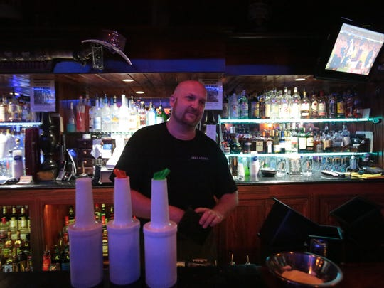 Chris the bartender serves patrons at Neil's Lounge in Indio during the Falcon v Buccaneers football game on TV on Thursday, September 18, 2014.