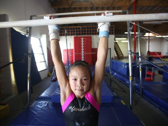 Tegan Nguyen is a 9-year-old gymnast, ranked as one of the top 100 in the country for her age group. In this photo she practices one of her two daily routines at Power Kids Center.