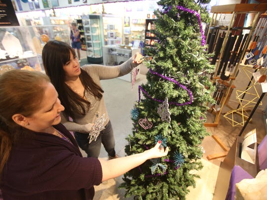 From left, Joy Meredith, owner of Crystal Fantasy, and Jennifer Hinton adorn a Christmas Tree at the specialty store in Palm Springs.
