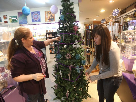 From left, Joy Meredith, owner of Crystal Fantasy, and Jennifer Hinton adorn a Christmas Tree at the specialty store in downtown Palm Springs.