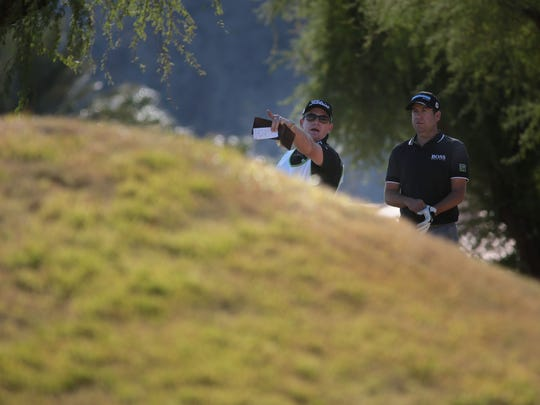 Erik Compton talks with his caddie on the eighth fairway of the Nicklaus Private Course during the third round of the Humana Challenge on Saturday. Compton shot a 5-under 67 on Saturday is part of a four-way tie for the lead.