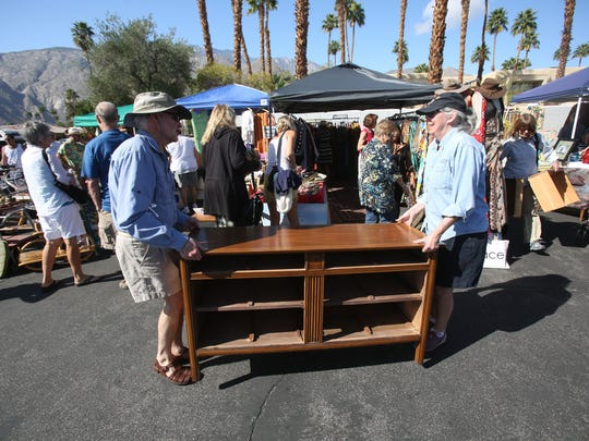 Two men carry their newly purchased piece of furniture at the sale Modernism Yard Sale held in Palm Springs.