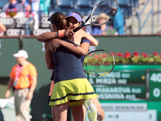 Martina Hingis, of Switzerland, and Sania Mirza, of India, hug after their 6-3, 6-4 win over the Russian pair of Elena Vesnina and Ekaterina Makanrova for this years BNP Paribas Open Women's Doubles title.