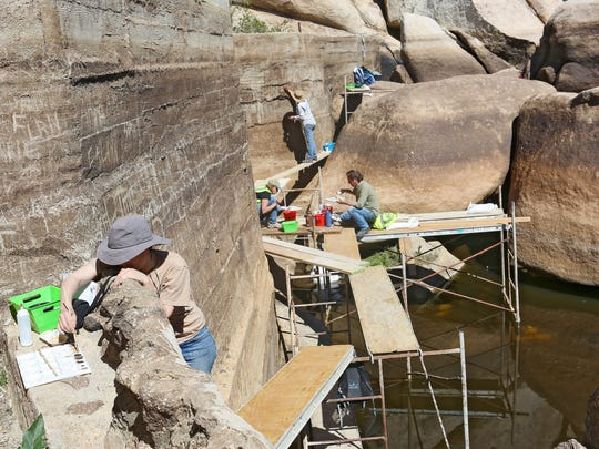 Katherine Shaum, an anthropology master's student at the University of New Mexico, works to restore Joshua Tree National Park's historic Barker Dam after years of graffiti on Friday, March 27, 2015.