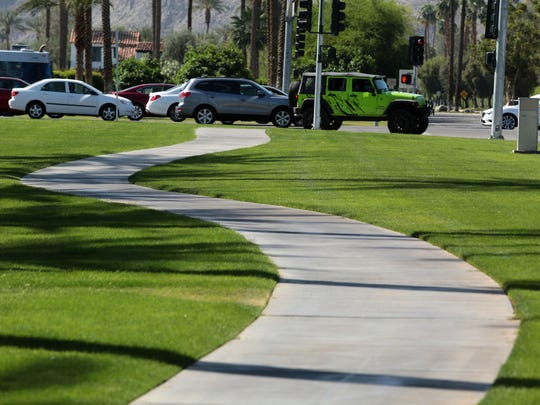 A sidewalk flanked by lush lawns run along Cook St. at the intersection with HWY 111 in Indian Wells on Thursday. The city uses recycled water to irrigate its medians and other grassy areas.