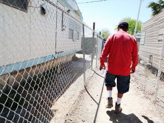 Mecca resident Roberto Mendez fills up his water bottle with drinking water from the tank provided by the nonprofit Pueblo Unido Community Development Organization in St. Anthony's Mobile Home Park on Thursday, April 16, 2015 in Mecca, Calif.