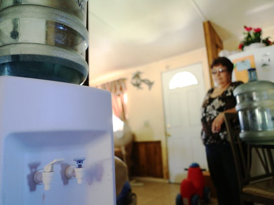 Mecca resident Carmen Vargas shows the drinking water she purchases for her mobile home located at the San Jose Community Center on Thursday, April 16, 2015 in Mecca, Calif.