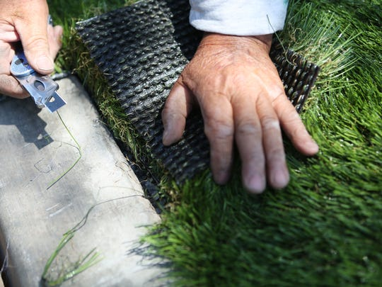 Back Nine Greens employee Hector Figueroa trims the edges from a piece of artificial turf to be installed for decorative use in front of a business on Monday in Palm Springs. Turf is becoming more acceptable among desert homeowners.