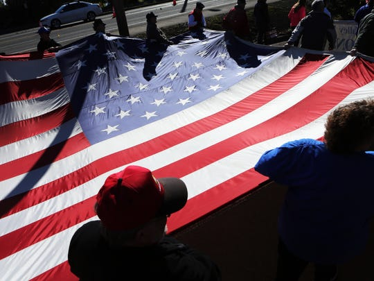 Marchers carry a giant American flag. Thousands of veterans and their supporters line the streets of Albany for the annual Veterans Day Parade.