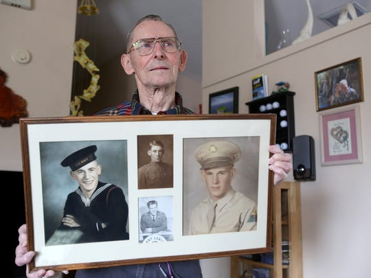 Albert Cole, who served on the USS Franklin during World War II, holds photos of himself, his father and his brothers, who also served in the military.