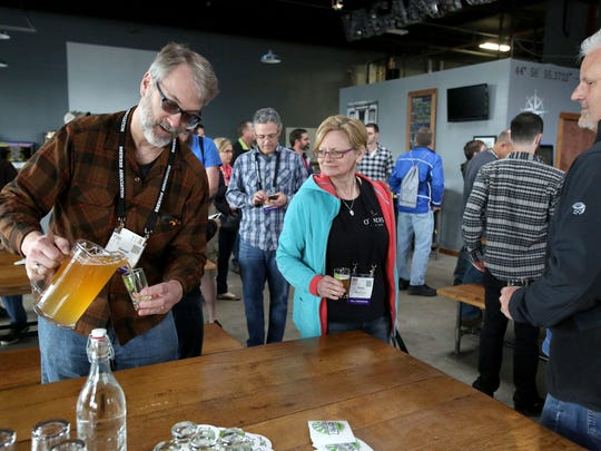 Daniel Justesen, left, of Minnesota, pours beer during a visit at Vagabond Brewing for a tour on Tuesday.