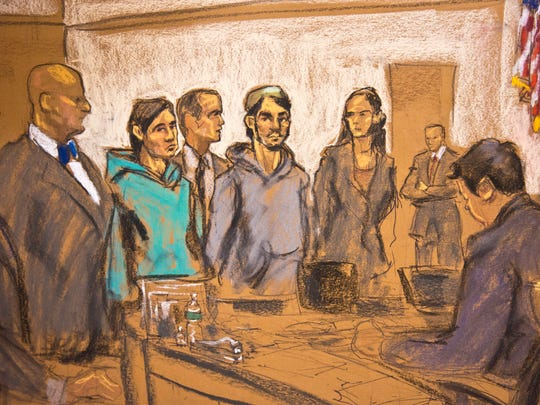 In this courtroom sketch, defendants Akhror Saidakhmetov, third from left, and Abdurasul Hasanovich Juraboev, fourth from right, stand in Federal Court at their arraignment Wednesday in Brooklyn, New York. They are charged along with a third man of plotting to travel to Syria to join the Islamic State group and wage war against the U.S.