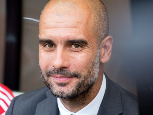 Munich's coach Pep Guardiola  smiles during the German soccer cup first round match between SC Preussen Muenster and FC Bayern Munich in Muenster, Germany, Sunday, Aug. 17, 2014. (AP Photo/Joerg Sarbach)
