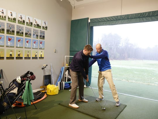 Rob Labritz, right, director of golf at GlenArbor Golf Club, works with Matt Thennes, 32, of Milford, Conn., at the club's indoor training facility Dec. 10, 2014.