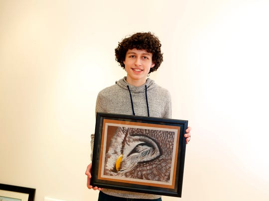 """Valhalla High School's Marc Charbonier, 16, with his work titled """"Owl By Myself"""" on Jan. 12 at OSilas Gallery in Concordia College in Bronxville."""