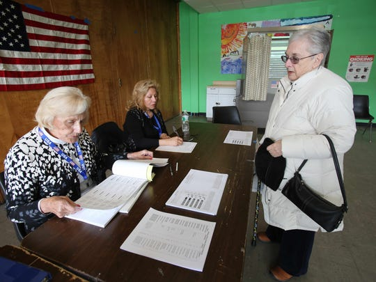 Letitia Chuckas, right, signs in with poll worker Patricia Barr, left, before voting in the Village Elections at Carver Center in Port Chester on March 18, 2015.