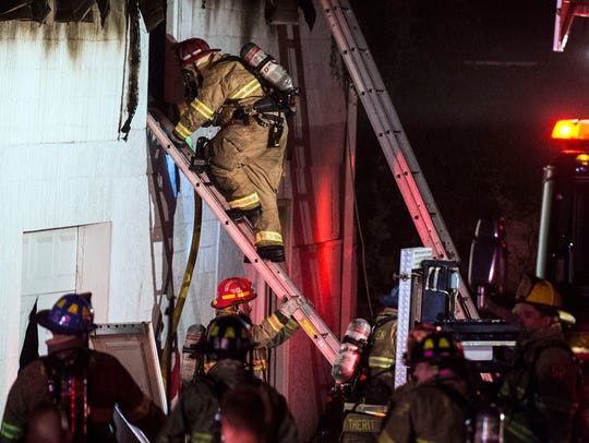A firefighter goes into the window of a garage to fight
