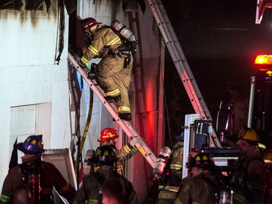 A firefighter goes into the window of a garage to fight the blaze, Tuesday, October 3, 2017. The fire was reported in the 200 block of East Chestnut Street around 8:14 p.m. According to Met-Ed, there are 1,122 customers without power in Hanover Borough.
