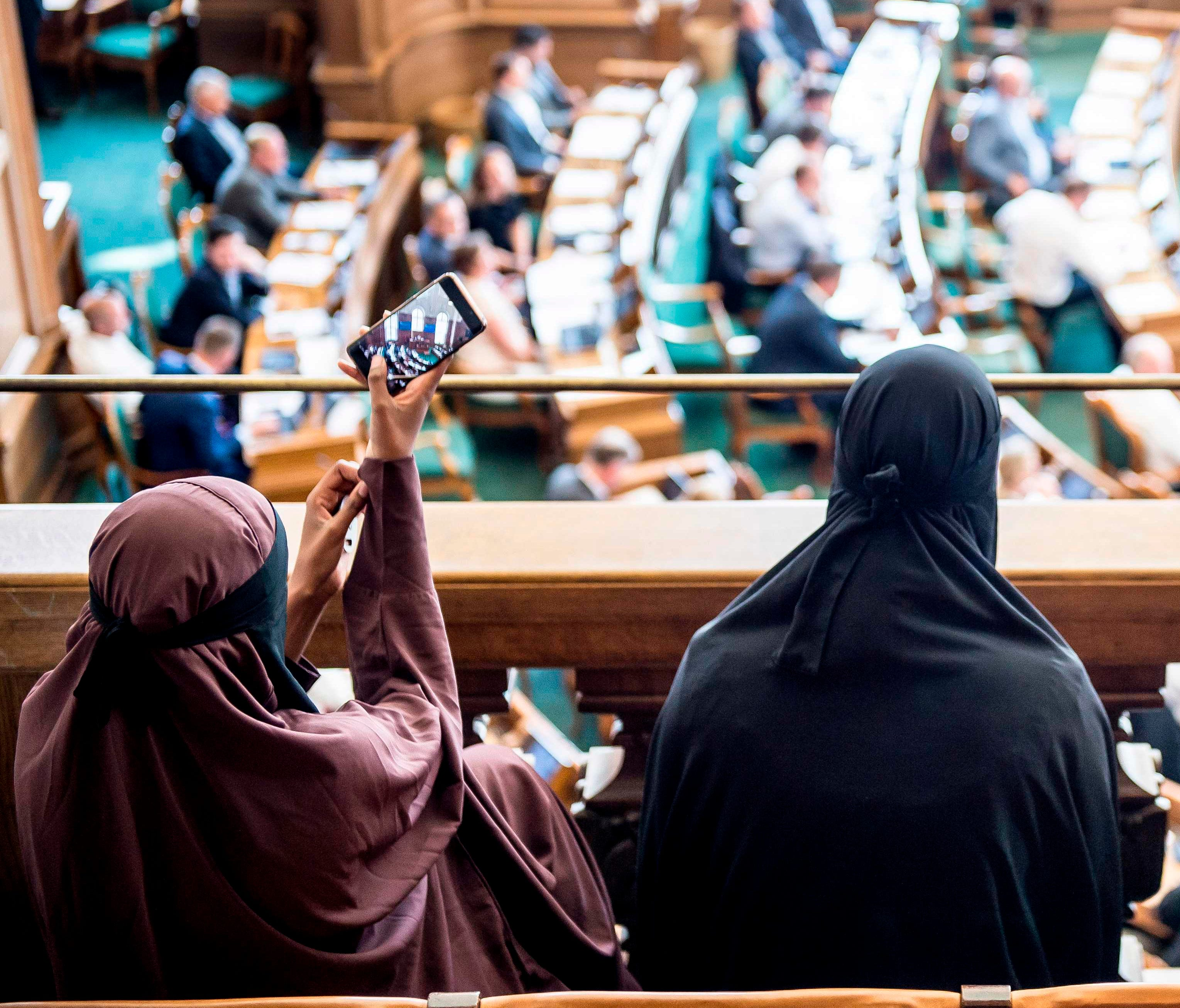 Women wearing niqab sit in the audience at the Danish Parliament in Copenhagen, Denmark, on May 31, 2018.   The Danish parliament on May 31,2018, passed a law banning the Islamic full-face veil in public spaces, becoming the latest European country to