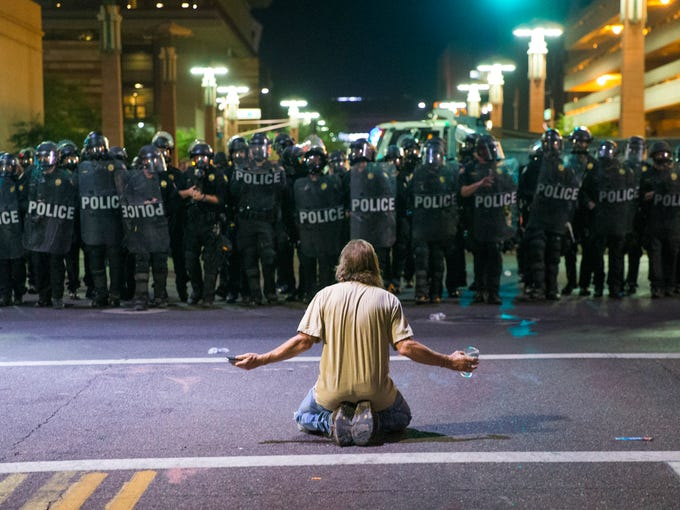 A protester sits on Second Street in front of a line