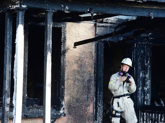 Maryland State Fire Marshal Carl Witmer looks at photos on the back of his camera while investigating the cause of a fatal fire that killed two people in Hagerstown, Md., Tuesday, Oct. 24, 2017.