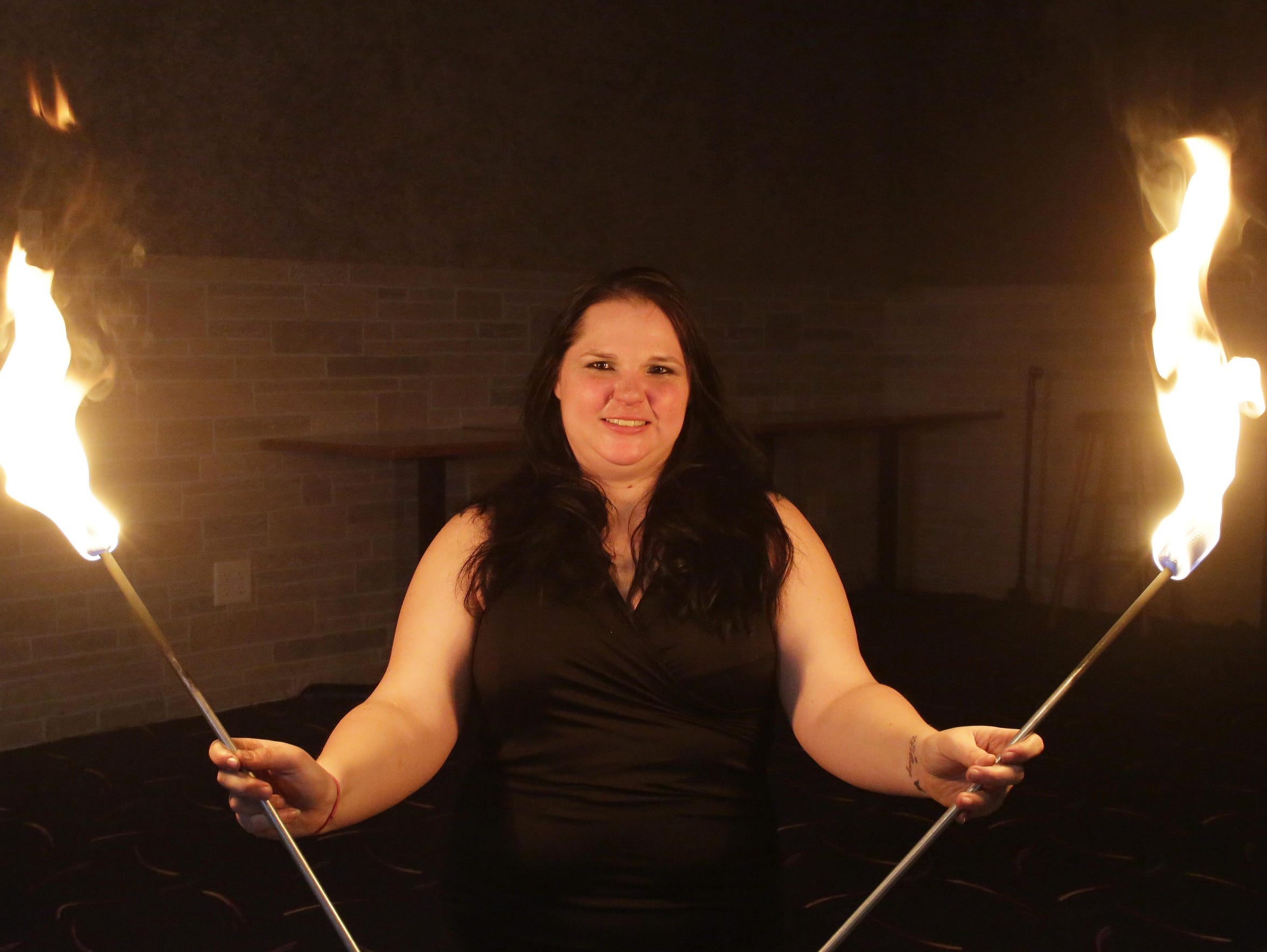 Valerie Ringwell of Sheboygan, poses with flaming fire batons, Thursday, April 12, 2018, in Sheboygan Falls, Wis. Ringwell is creating a calendar after being sexually assaulted with hopes to help others with assault recovery. She learned how to eat fire so she could conquer one of her fears.