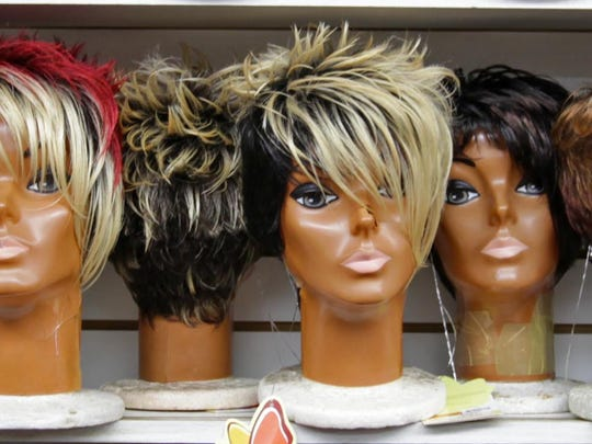 Mannequin heads with wigs for sale line up on a shelf at Downtown Wig on N. Market Street.