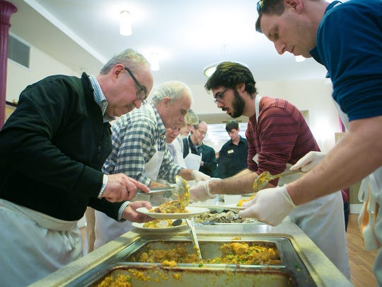 Wilmington restaurateur, Xavier Teixido (left), joins other volunteers as they plate the paella dish.