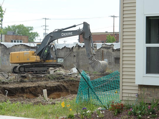 A backhoe demolishes two houses on Van Buren Street