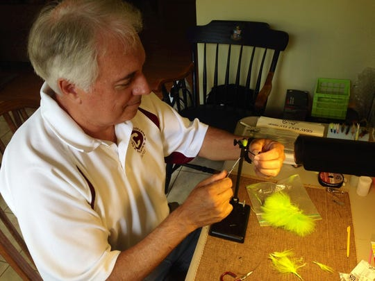 """Glenn """"Catch"""" Cormier, who revived the Kisatchie Fly Fishers club two years ago, ties a fly at his work desk."""