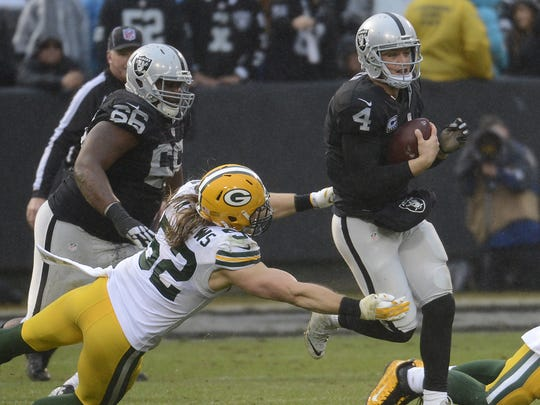 Green Bay Packers inside linebacker Clay Matthews (52) dives to tackle Oakland Raiders quarterback Derek Carr (4) in Oakland.
