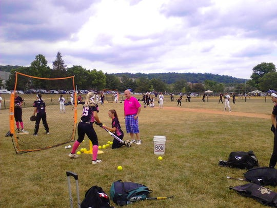 Coach Lou Bishop works with TC Tremors 3N2 Gold 18U players  Lacy O'Donnell, left, and Hunter Levesque at a hitting station before a game at the Team NJ National Showcase in Edison, New Jersey.