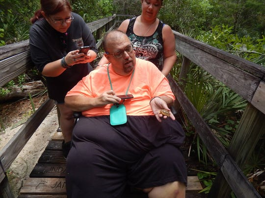Fred Riley examines a small turtle in March 2015 at Turkey Creek Sanctuary in Palm Bay with nieces Micheala Snuffer (left) and Tabitha Lincoln.