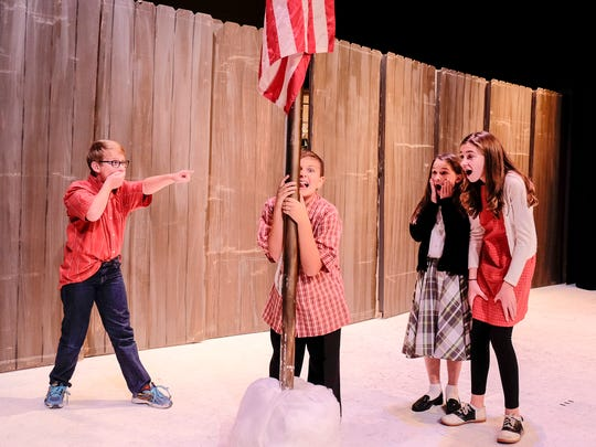 Flick, played by Alex Dupuy, is surrounded while his tongue is stuck to a flag pole. His onlookers are from left, Schwartz (played by Carter Emerson), Elizabeth Luter, a member of the ensemble, and Celia Dupuy, another member of the ensemble.