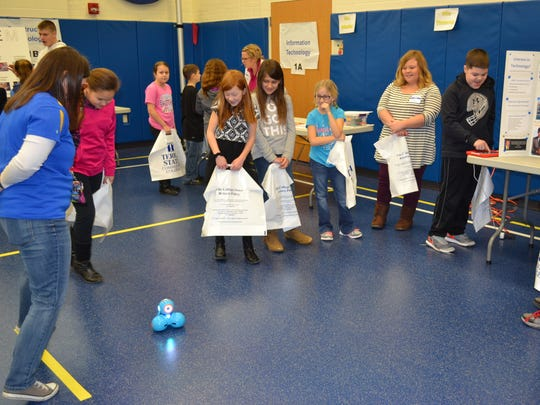 Students watch Dash, a robot, scoot across the floor during the Third Grade Career Fair. Dash was brought to the event by Terra computer science instructor Haley Crabtree, third from right.