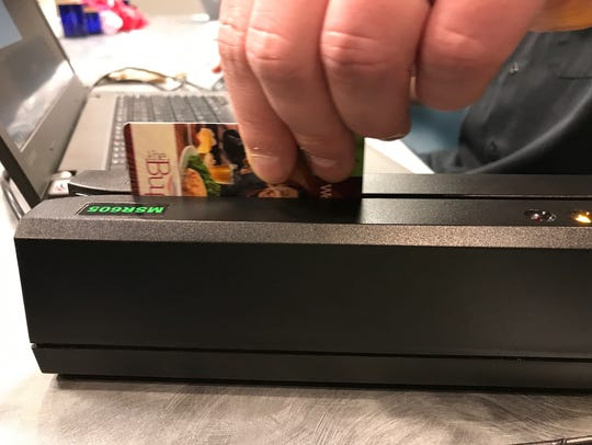 A hotel card key being swiped through a card reader.