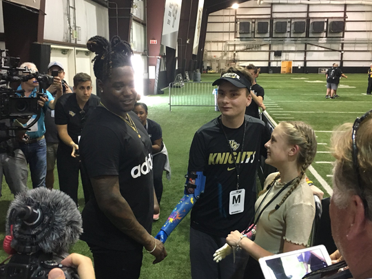 Wyatt Falardeau (center) and Anni Emmert (right), meet University of Central Florida linebacker Shaquem Griffin, at Griffin's Pro Day on March 29, 2018, at the UCF fieldhouse in Orlando. Griffin, who has one hand, works with Limbitless Solutions, an organization that supports children in need of prosthetic limbs. Both Falardeau and Emmert have received a prosthesis from Limbitless Solutions.