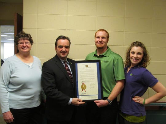 A signed proclamation from Gov. Scott Walker stating March is brain injury awareness month was presented at N.E.W. Curative Rehabilitation in Green Bay on Feb. 24, 2015. Pictured from left to right are Sandy Rieth, Green Bay Mayor Jim Schmitt, Gary Rieth and Bari York.