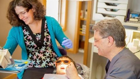 Bernadette Spink, RDH, left, and Dr. George Knoedler, D.D.S. of Mosinee, work on a patient's teeth.