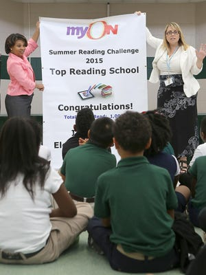 Principal Tisa Day, left, and Jackson-Madison County School System Literacy Coordinator Jean Little present a banner to the students who read the most books in the myON Summer Reading Program on Wednesday at Isaac Lane Elementary.