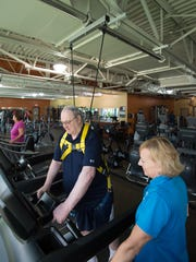 Bob Seaberg of Magnolia walks on a treadmill using a support harness as Beth Johnson a wellness coordinator at the Dover YMCA monitors his fitness workout.